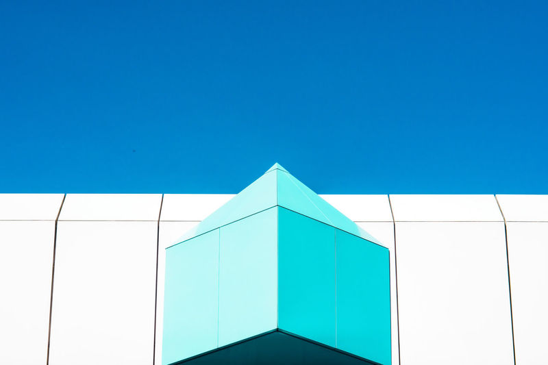 Low angle view of modern building against clear blue sky