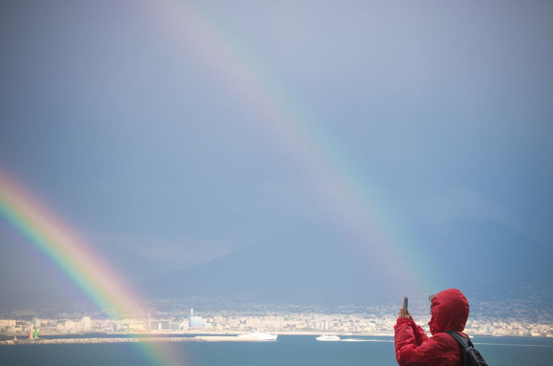 Woman Photographing Double Rainbow And Lake