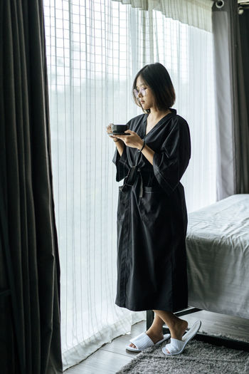 Young woman using phone while standing on bed at home