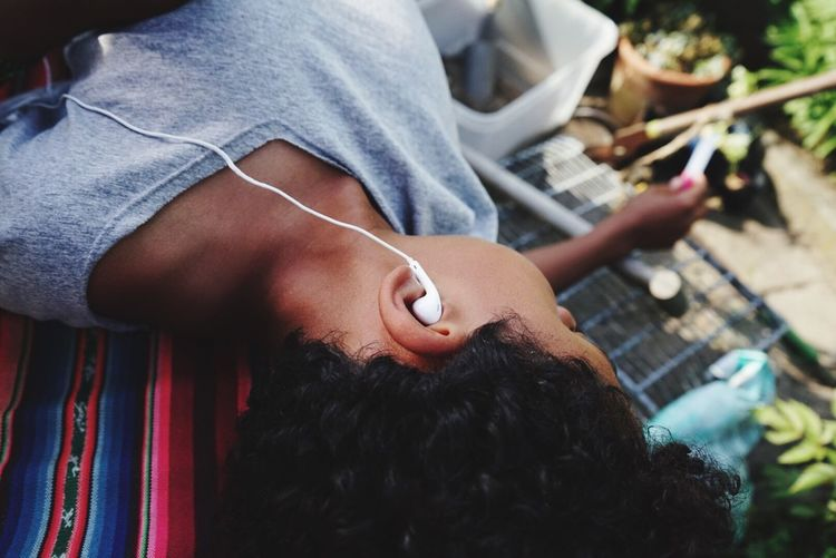 High angle view of boy listening music while relaxing outdoors