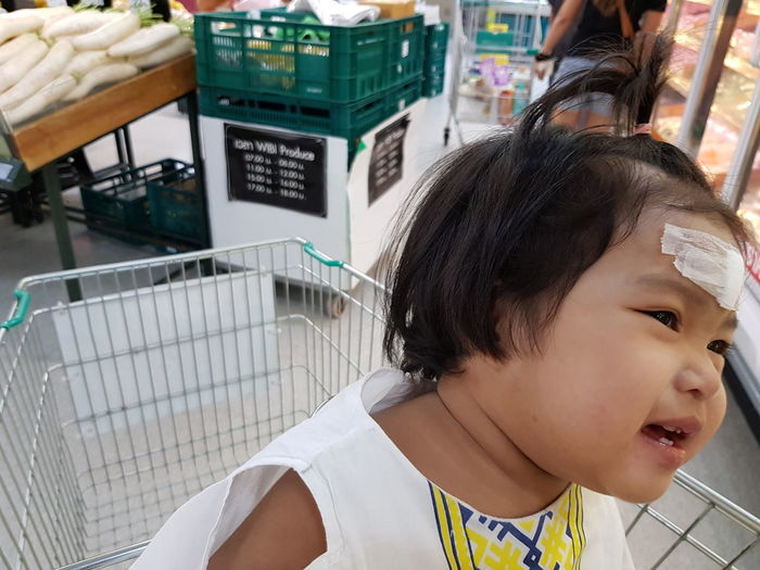 Close-Up Of Cute Girl Sitting On Shopping Cart In Supermarket