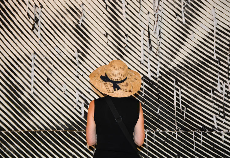 Woman standing in front of striped wall