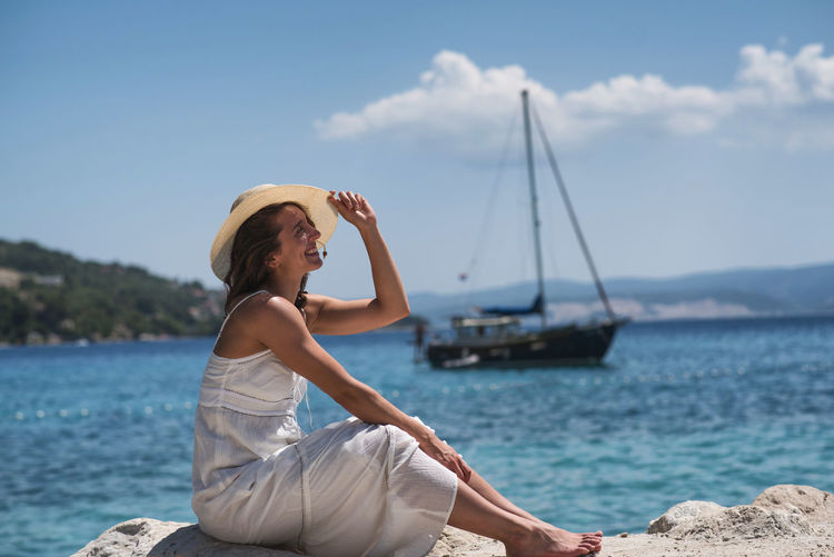 woman on beach enjoying sun Adult Freedom Hat Headwear Leisure Activity Nature Nautical Vessel One Woman Only Outdoors People Relaxation Sea Sea And Sky Seaside Sitting Tranquility Travel Travel Destinations Vacations Water