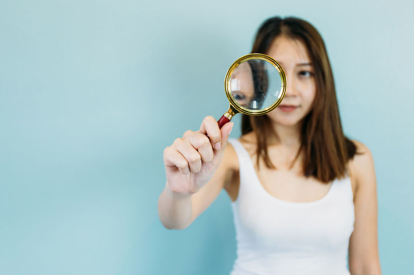 Young Asian woman with magnifying glass isolated on a blue pastel background Asian  Beautiful Research Woman Day Detective Discovery Eye Eyesight Front View Holding Inspection Lens Flare Magnifying Glass One Person People Real People Searching Spy Standing Studio Shot Vision Watching Young Adult Young Women