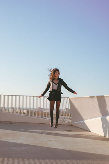 Woman levitating against clear sky
