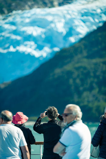 Rear view of people photographing on mountain