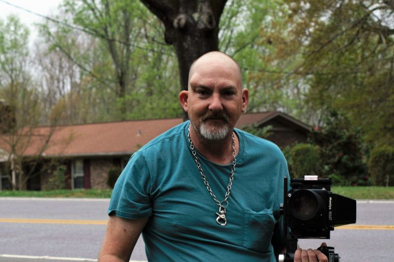 Portrait Of Mature Man With Camera On Street