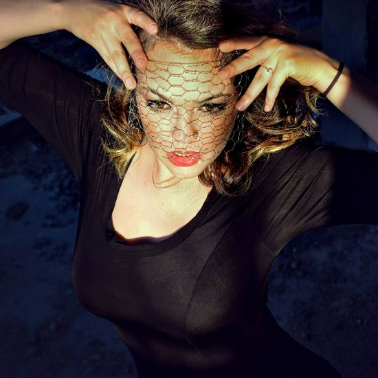Young Woman Holding Net On Face