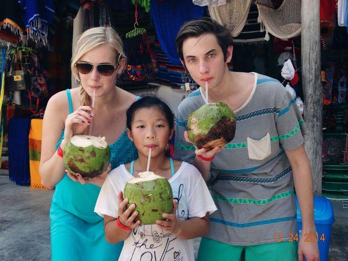 Portrait of family drinking coconut water in market
