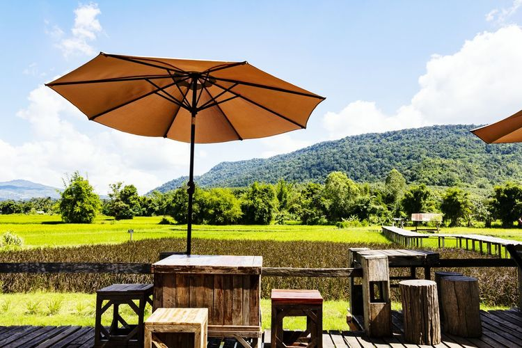 Living outdoor in the nature among mountain tree and clear sky. Nature Blue Chair Table View Landscape Fresh Holiday Relax Environment Tree Summer Sky Cloud - Sky Umbrella Sun Lounger Under Below Monsoon Sunshade Parasol Agricultural Field Farmland Plough Bale  Thatched Roof Cultivated Land