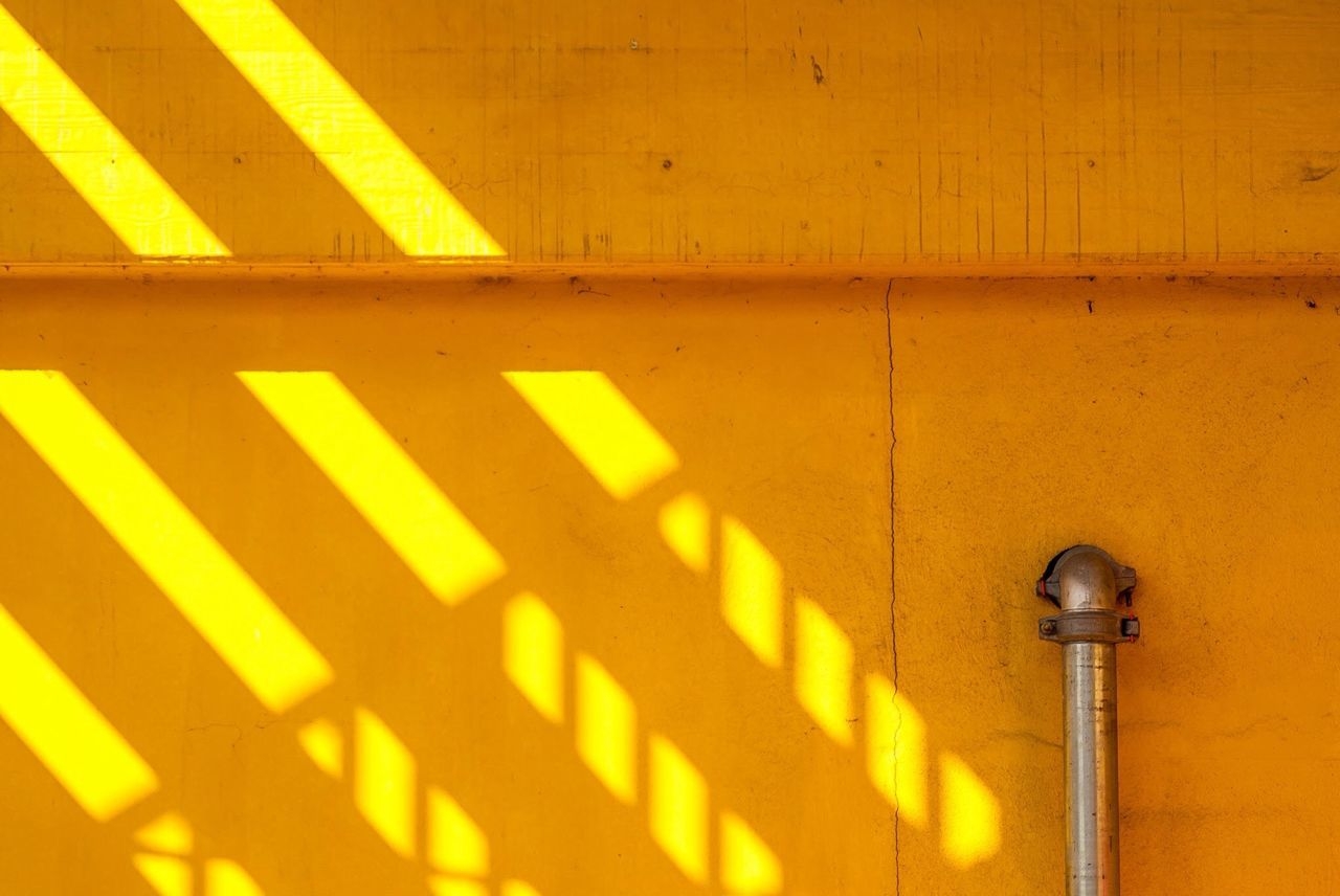 Close-up of cropped railing and sunlight on yellow wall
