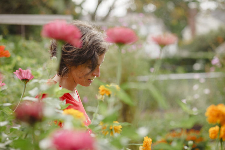 Rear view of woman with red flowering plants