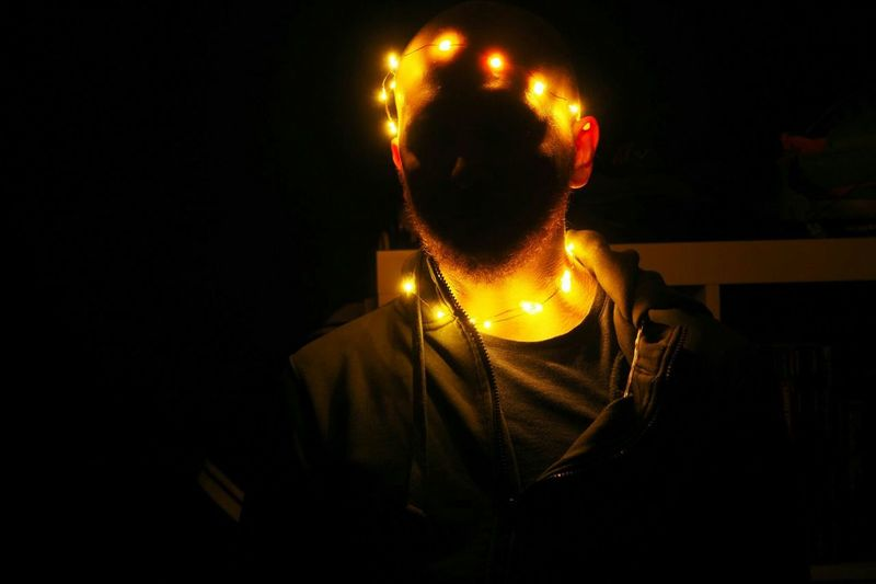 Man sitting in illuminated lighting equipment