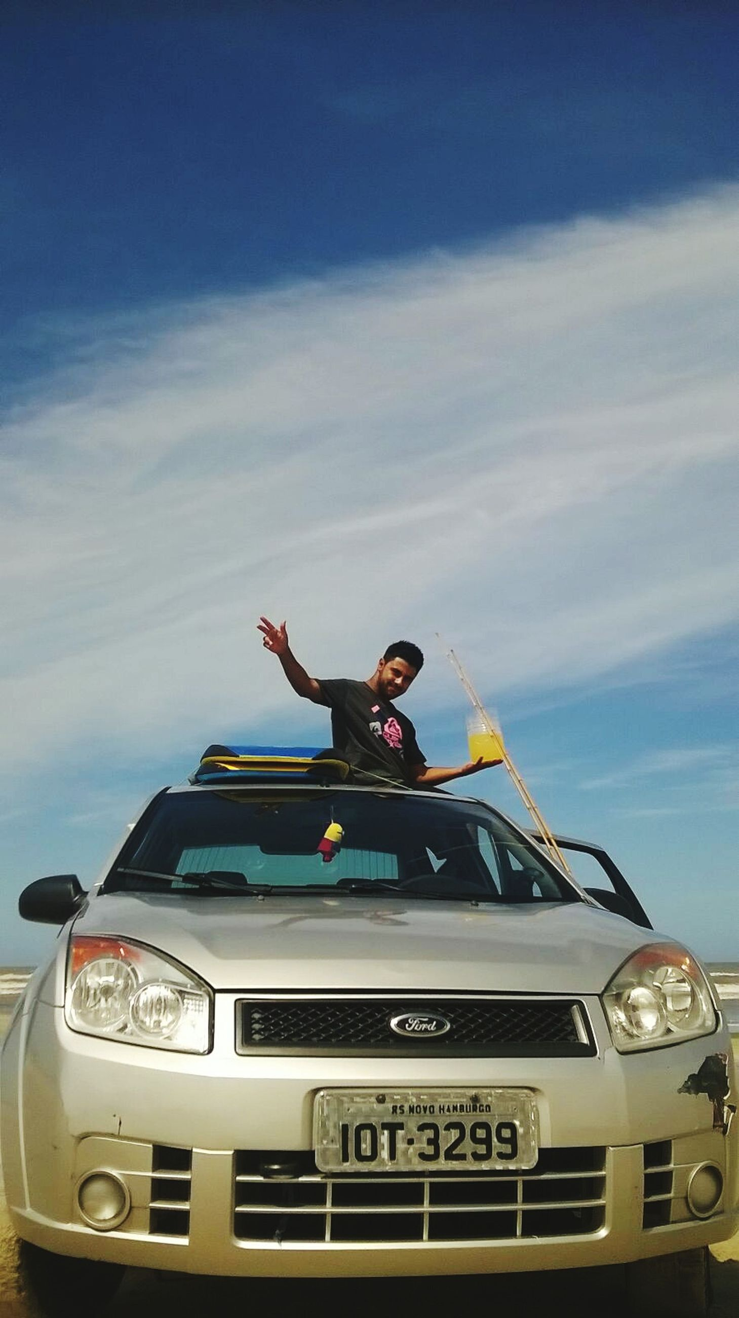 person, young adult, lifestyles, mode of transport, transportation, low angle view, leisure activity, sky, young men, front view, casual clothing, full length, looking at camera, sitting, smiling, cloud - sky, land vehicle, travel