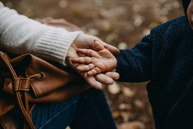 Midsection of couple holding hands during winter