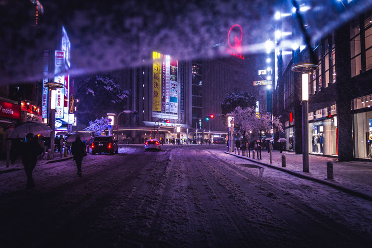 Snow covered street in illuminated city at night