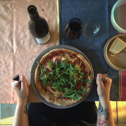 Cropped image of hand with pizza and wine on table