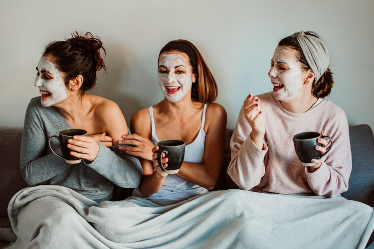 Cheerful female friends with facial masks holding mugs while sitting against wall at home
