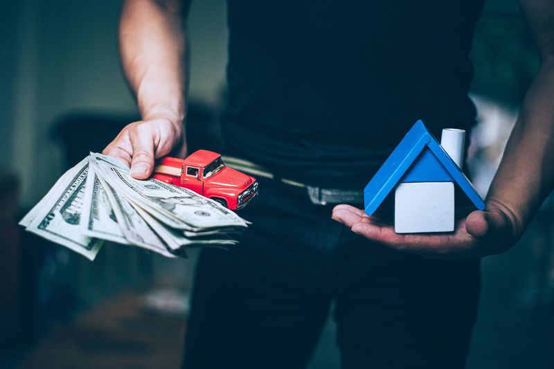Midsection Of Man Holding Paper Currency And Toy Car With Model Home