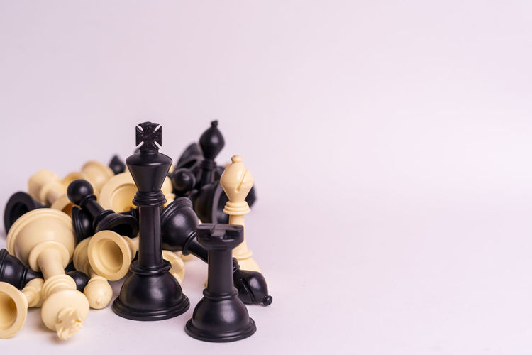 Chess set on white background. Indoors  Chess Game Competition Queen King - Royal Person King Army Strategy Leader Leadership Decisions Board Game Leisure Games Chess Piece Copy Space Studio Shot Relaxation Chess Board King - Chess Piece Arts Culture And Entertainment Leisure Activity No People Black Color Defeat Conflict Colored Background Pawn - Chess Piece Knight - Chess Piece Queen - Chess Piece Aggression