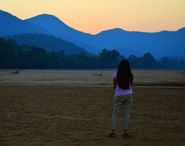 Rear view of woman standing on field against mountains during sunset