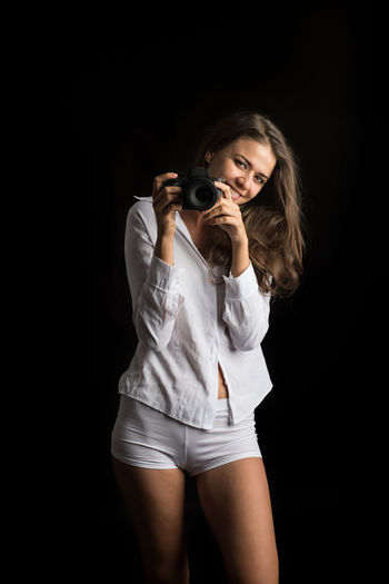 One Person Black Background Holding Studio Shot Young Adult Standing Camera - Photographic Equipment Three Quarter Length Photography Themes Hair Indoors  Beauty Front View Portrait Photographing Young Women Beautiful Woman Activity Beautiful People Hairstyle Shorts Photographer