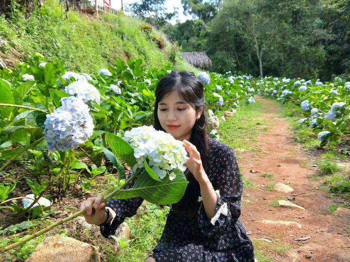 Portrait of girl holding flowering plants