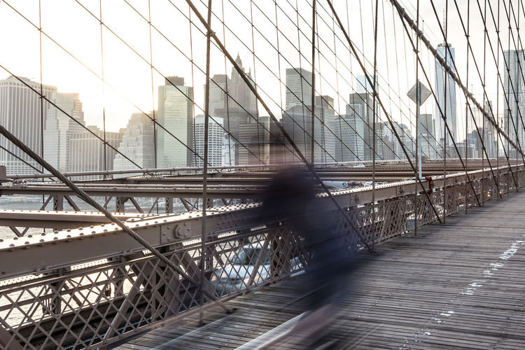 Man walking on footbridge in city against sky