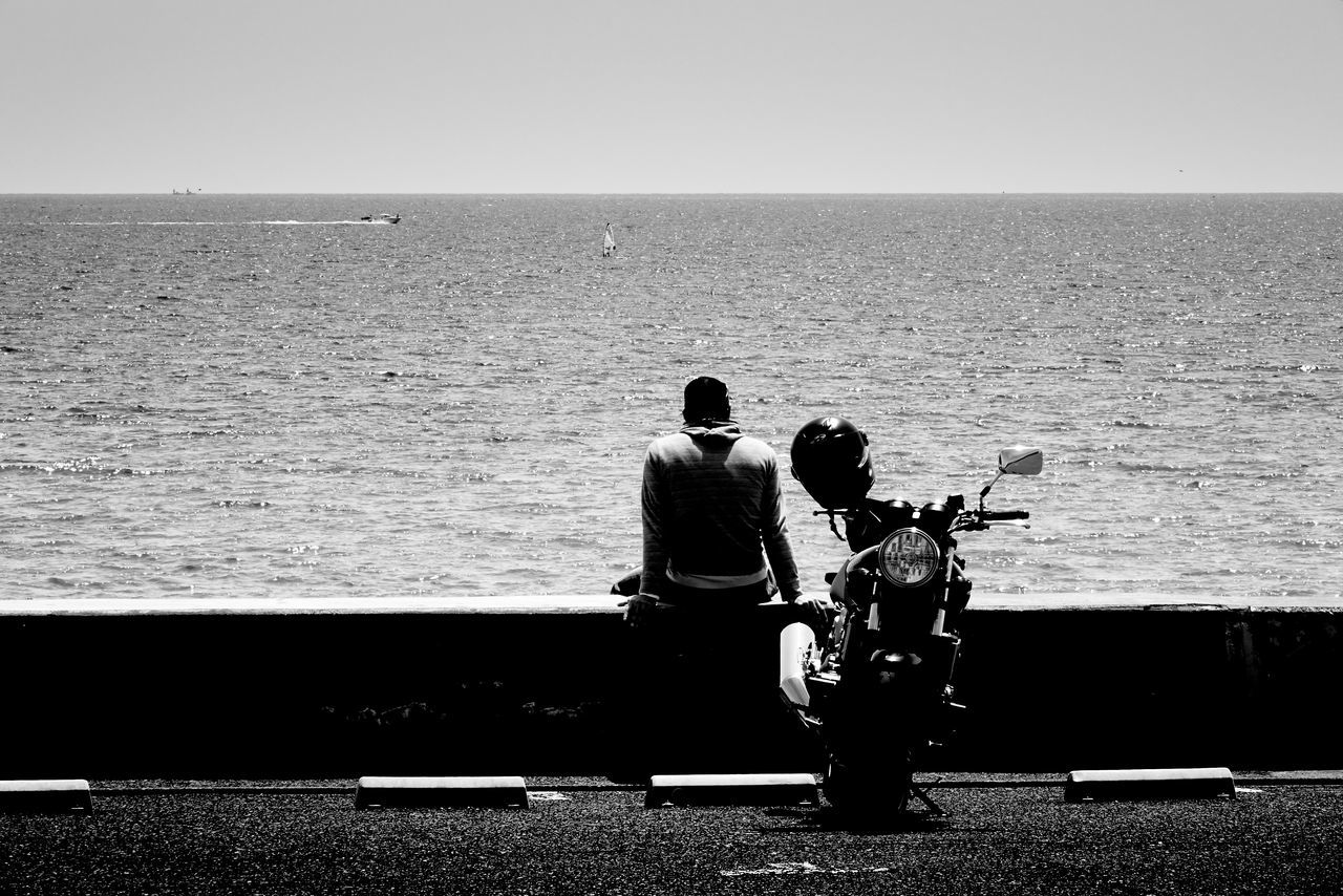 Rear View Of Man With Motorcycle Relaxing On Retaining Wall Against Sea