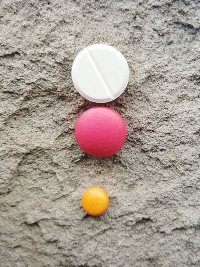 pills tabletes medicine on cement Color Code Pilule Pills Tablettes Top View Cement Capsule Medicine Healthcare And Medicine Healthcare Pink Antidepressant Painkillers Yellow Pink White Mental Health  Flu High Angle View Close-up Colorful Multi Colored