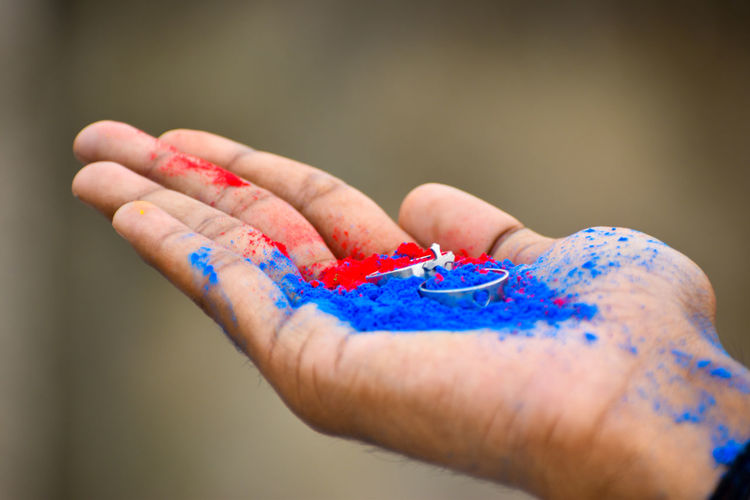 Cropped hand of woman holding powder paint with ring outdoors
