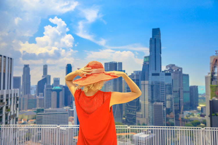 Lifestyle woman with wide hat enjoys panorama from one of Singapore's tallest skyscrapers above Chinatown. Aerial view of cityscape skyline. Caucasian tourist looking financial district in downtown. Singapore Singapore City Woman Tourist Tourist Attraction  Tourist Destination People Girl Females Aerial View Skyline Cityscape Panorama Happy Travel Hat Lifestyle Enjoy Nature Tourism Building Exterior Architecture Built Structure One Person City Building Standing Sky Office Building Exterior Landscape Urban Skyline Waist Up Skyscraper Adult Women Day Cloud - Sky Holding Outdoors Human Arm Hand Modern Human Limb