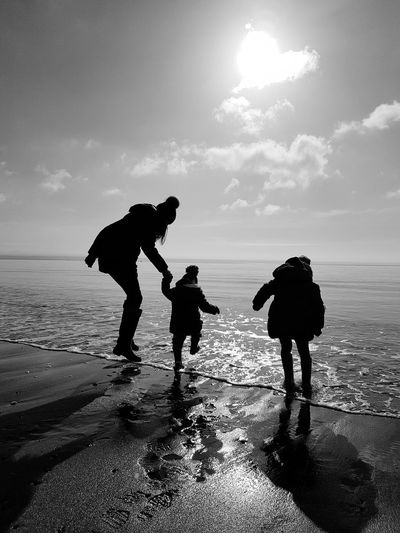 Beaches and Bobblehats - b&w Holiday Holidays Jumping Waves Sun Sunshine Heart Shaped Sun Love Fun Happy Wave Jumping Family Water Sea Togetherness Beach Child Childhood Children Wave First Eyeem Photo EyeEmNewHere Coast Young Family