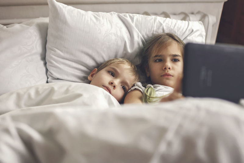 Siblings watching video in mobile devices in bed, gadget dependence and addiction, online lifestyle