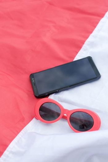 High angle view of sunglasses on mobile phone