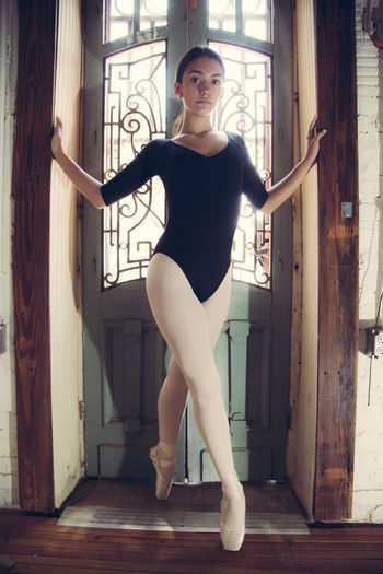 Portrait of young woman ballerina posing on doorway at home