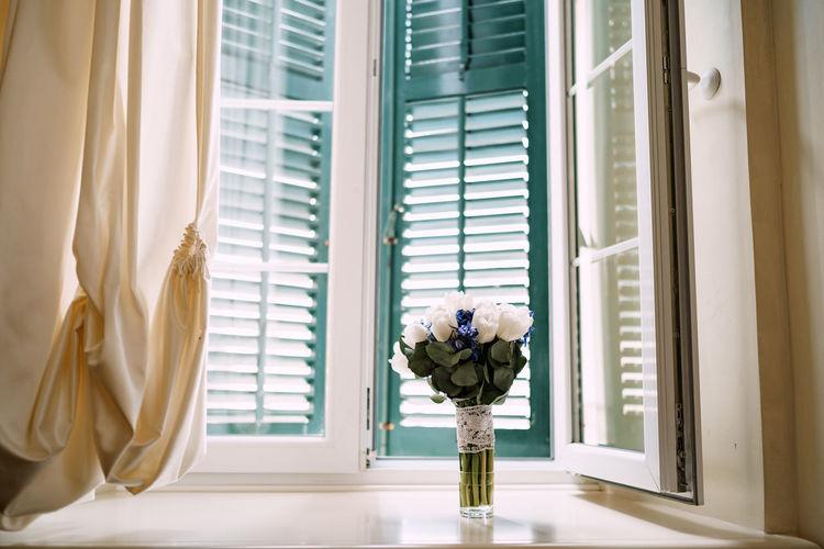 White flowers in vase on window sill