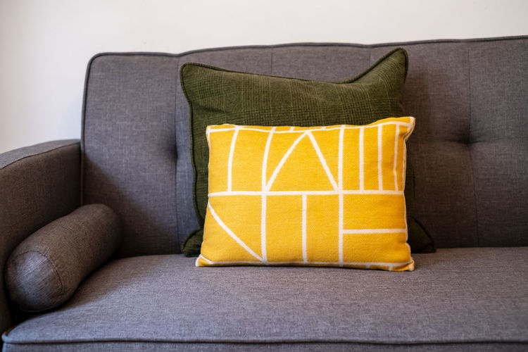 Close-up of yellow chair on sofa at home