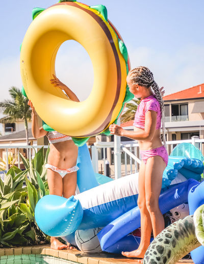 poolside fun with inflatables- young girls in swimsuits having a fun summer day by the pool Childhood Child Girls Real People Females Women Lifestyles Full Length Day Leisure Activity Holding People Happiness Clothing Tube Innocence Outdoors Swimming Pool Inflatable  Vacations Summer