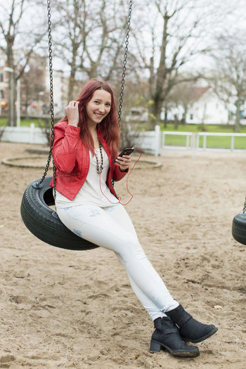 Portrait of smiling young woman sitting on swing