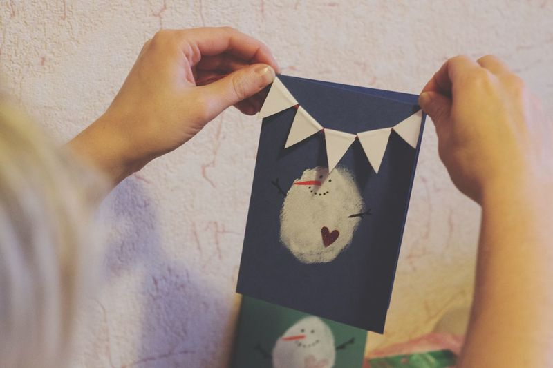 Cropped hands of woman holding greeting card at home
