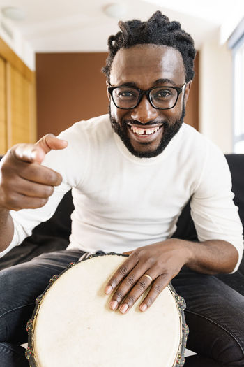 Portrait of smiling young man playing tambourine at home