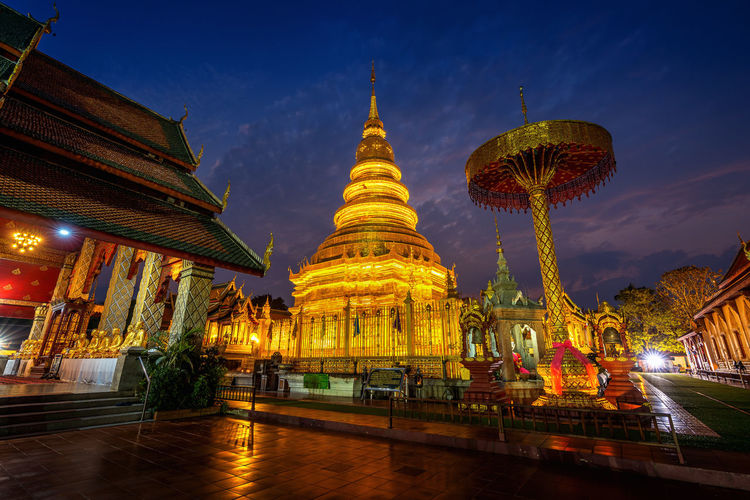 Wat Phra That Hariphunchai temple in Lamphun, Thailand. Belief Architecture Place Of Worship Religion Built Structure Spirituality Building Building Exterior Sky Illuminated History Travel Destinations Pagoda The Past Tourism Gold Colored Travel Nature No People Outdoors Spire  Ornate