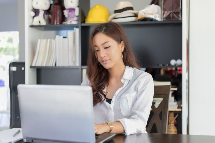 Young Businesswoman Using Laptop On Table At Office