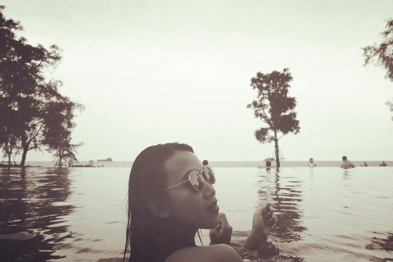 Young woman with sunglass in infinity pool against clear sky