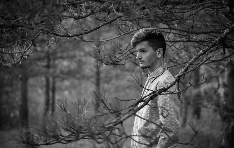 Man looking away on bare tree