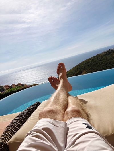 Man relaxing legs on a lounge chair on a tropical beach overlooking ocean. Copy Space Cabo San Lucas Mexico Low Section Personal Perspective Lifestyles Outdoors Swimming Pool Ocean View Water Human Leg Relaxation Horizon Over Water Sea Leisure Activity Laying Down Clear Sky Summer Hillside Beach View Tropical Climate Lush Foliage Horizon Over Land barefoot Sunny Day It's About The Journey