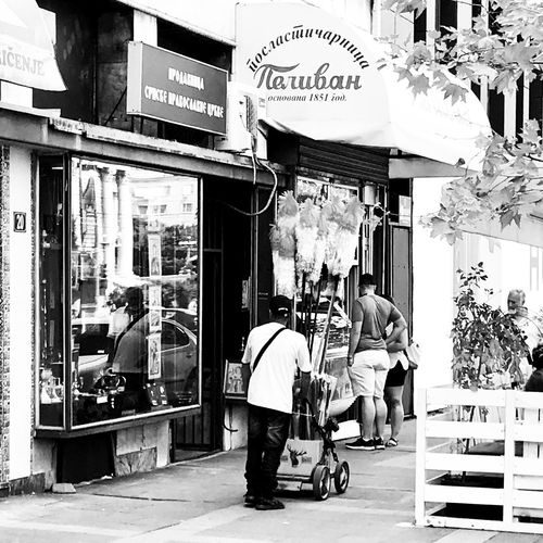 Pelivan Dusters Streetvendor Black And White Photography BW_photography Blackandwhite Photography Street Photography Streetphoto_bw Reflection Belgrade,Serbia Men Text City Real People Street Day Architecture People Store City Life Lifestyles Building Exterior Outdoors Built Structure