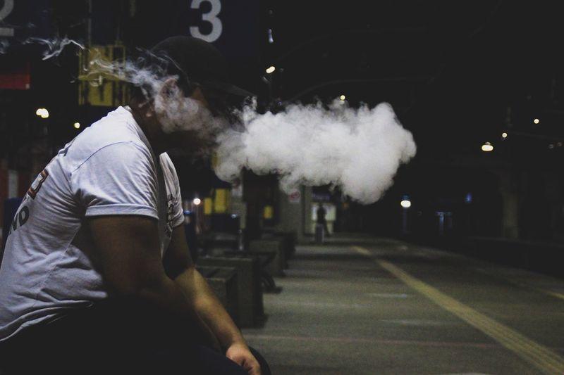 Side view of man exhaling smoke while sitting at railroad station platform