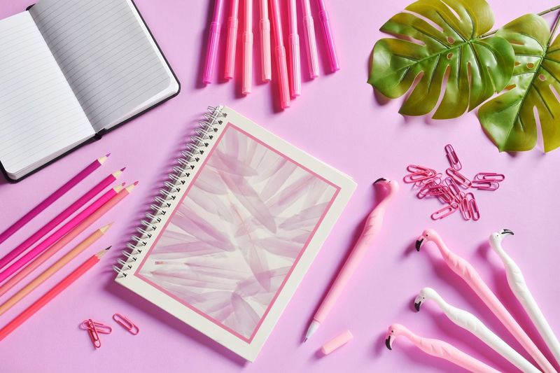 High angle view of books with pens and paper clips on pink background